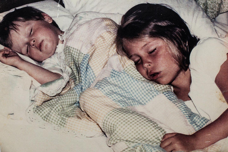 Zwei kleine Kinder schlafen in einem Bett