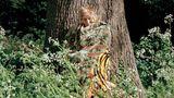 Ein älterer Mann steht in einer tarnfarbenen Decke vor einem Baum