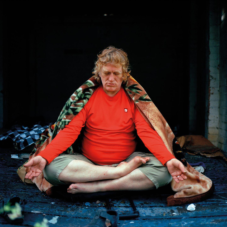 Ein älterer Mann meditiert im Schneidersitz
