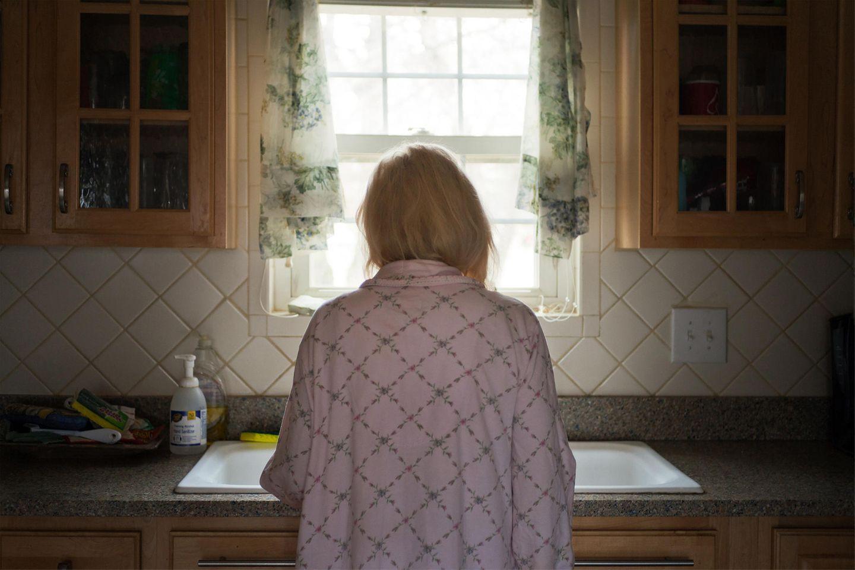 Spitz' Mutter steht im Morgenmantel in der Küche an der Spüle