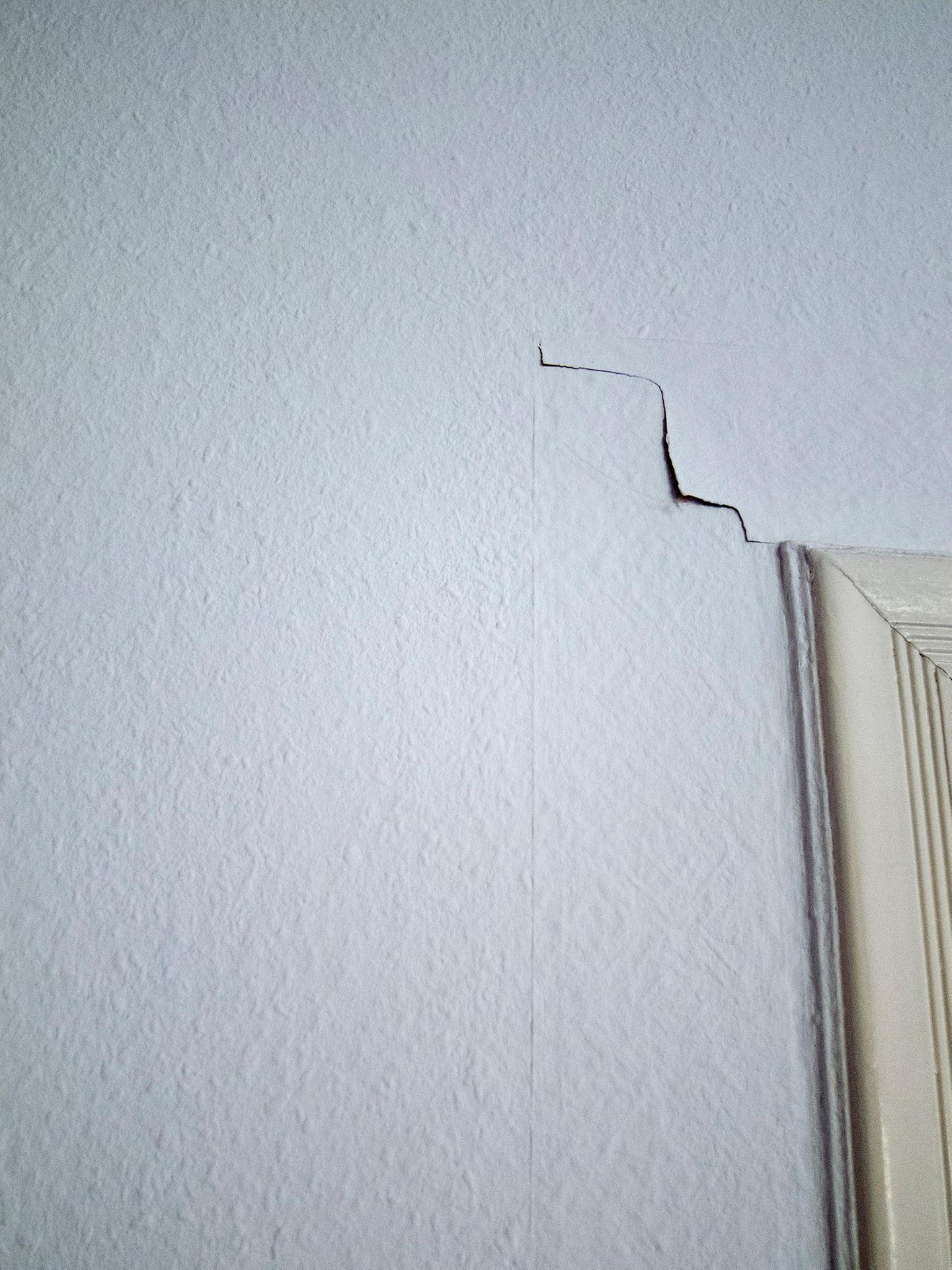 Über einem Türrahmen geht ein Riss durch die Tapete