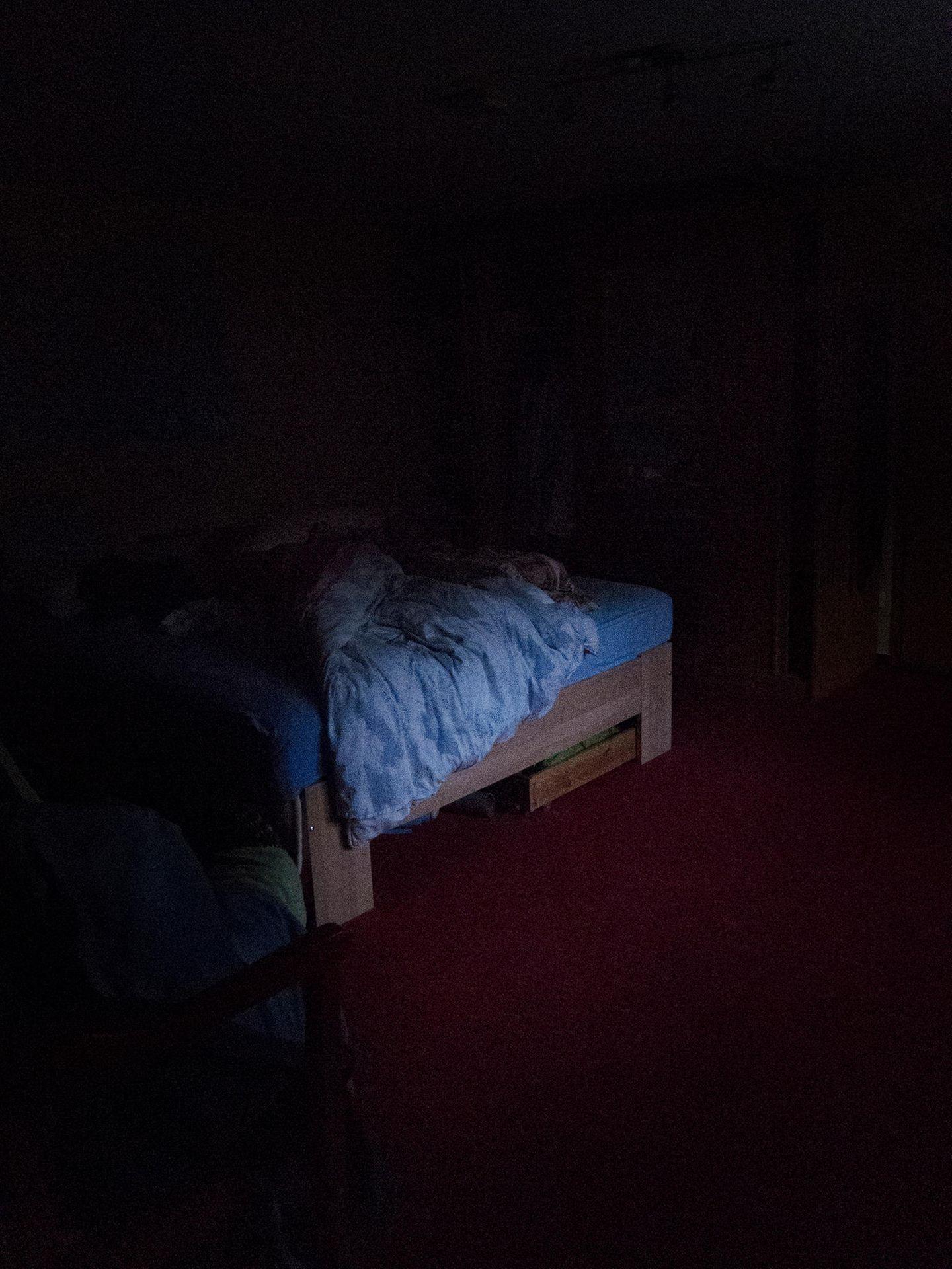 Ein Bett steht in einem abgedunkelten Zimmer