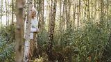Eine alte Frau steht in einem Birkenwald