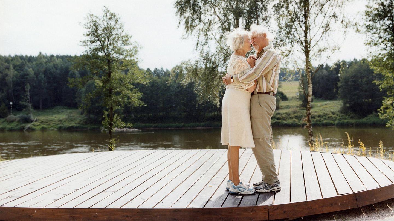 Das alte Ehepaar umarmt sich an einem Fluss stehend