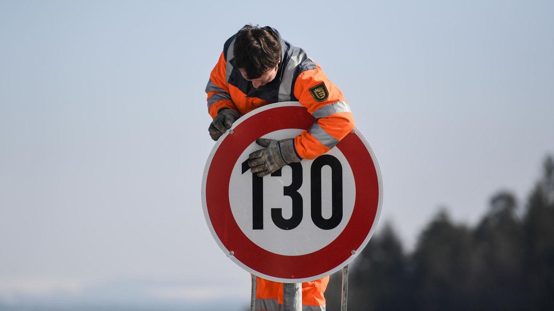 Ein Straßenwärter montiert an der Autobahn A81 am Hegaublick ein Schild mit der Aufschrift «130»