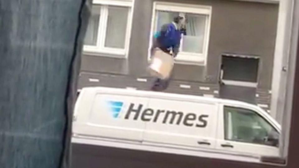 Ein Hermes-Bote wirft ein Paket auf den Balkon.