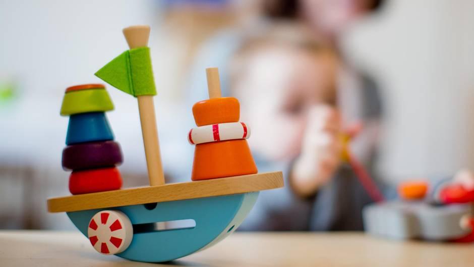 Ein Kind spielt in einer Kita mit Holzspielzeug