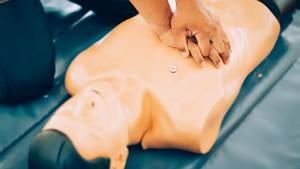 Ein Mann, der an einer Puppe eine Herzdruckmassage übt