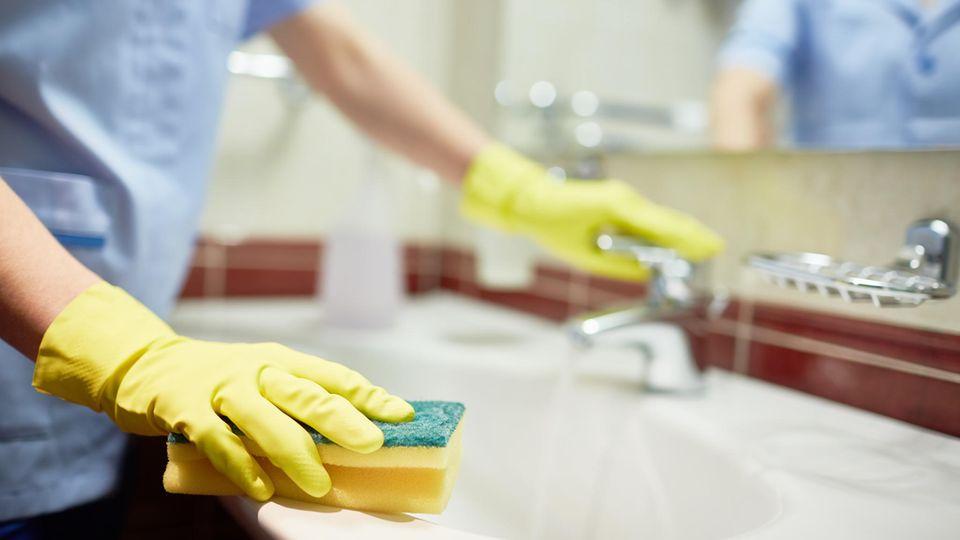 Eine Frau, die ein Waschbecken putzt
