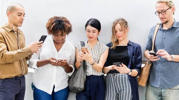 Fünf Menschen schauen auf ihr Smartphone
