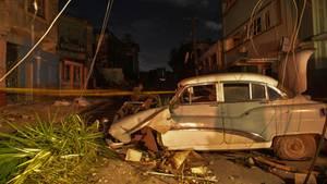 Ein vom Sturm zerstörter Oldtimer steht unter abgerissenen Strom- und Telefonkabeln. Neben dem Wagen liegen Pflanzen