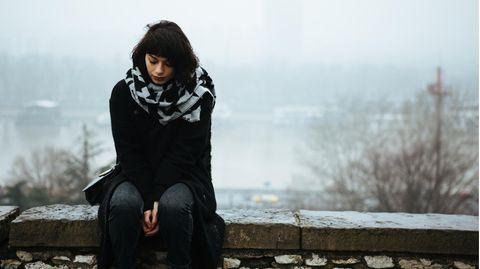 Ein Mann sitzt allein auf einer Bank und raucht