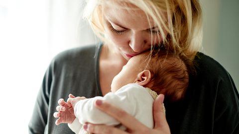 Herpes-Viren: Eine Frau küsst ein Neugeborenes auf die Stirn