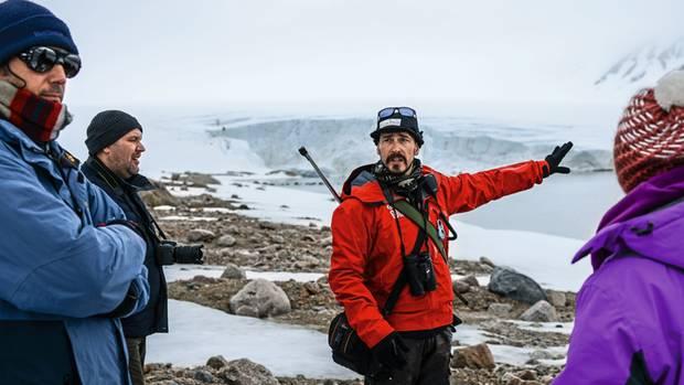 Rémis erklärt Gästen die Entstehung von Gletschern. Wie alle Guides ist auch er bei Landgängen bewaffnet, falls ein Eisbär auftauchen sollte.