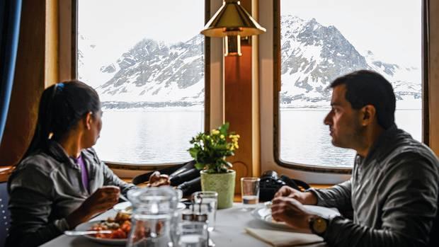 Während Swati und Karan aus Indien an Bord essen, blicken sie auf schneebedeckte Berge