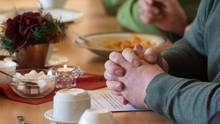 """Ein Mann sitzt mit gefalteten Händen an einem Tisch im """"Restaurant des Herzens""""der Evangelischen Stadtmission Erfurt"""