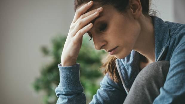 Burnout im Privatleben: Eine Frau ist erschöpft und fasst sich an den Kopf