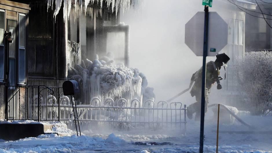 Ein Feuerwehrmannim Einsatz während einesBrandes in einem Wohnhaus in St. Paul. Das Löschwasser sorgt für die Entstehung von bizarren Eiszapfen.
