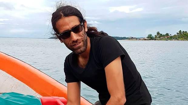 Behrouz Boochani sitzt lächelt auf einem Boot