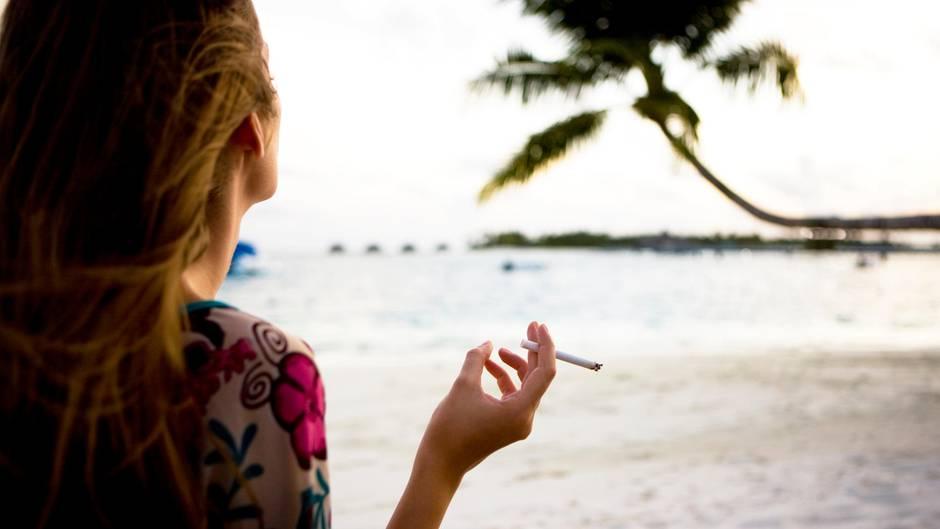 Eine Frau mit langen Haaren raucht eine Zigarette auf einem Palmenstrand