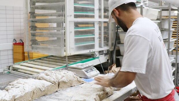 Semiallah war ein halbes Jahr auf der Flucht nach Deutschland. In der Bäckerei Soetebier hat er eine neue Perspektive gefunden – er macht eine Ausbildung zum Bäcker. Hierbereitet geradeden Teig fürRoggen-Kürbis-Brötchen vor.