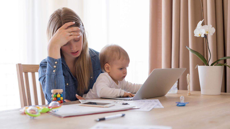 Eine Mutter am Laptop mit Baby auf dem Schoß