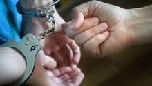 Zwei Hände in Handschellen