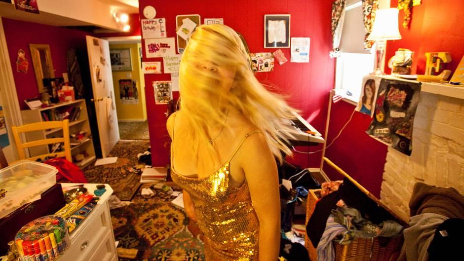 Teenagerin in unaufgeräumtem Zimmer