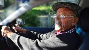 Älterer Herr fährt Auto und hat die Hände am Lenkrad