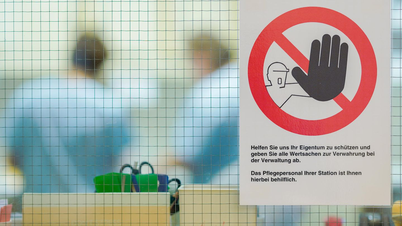 Ein Warnschild gegen mögliche Diebstähle hängt an der Glasscheibe eines Stationszimmers des KlinikumsMannheim