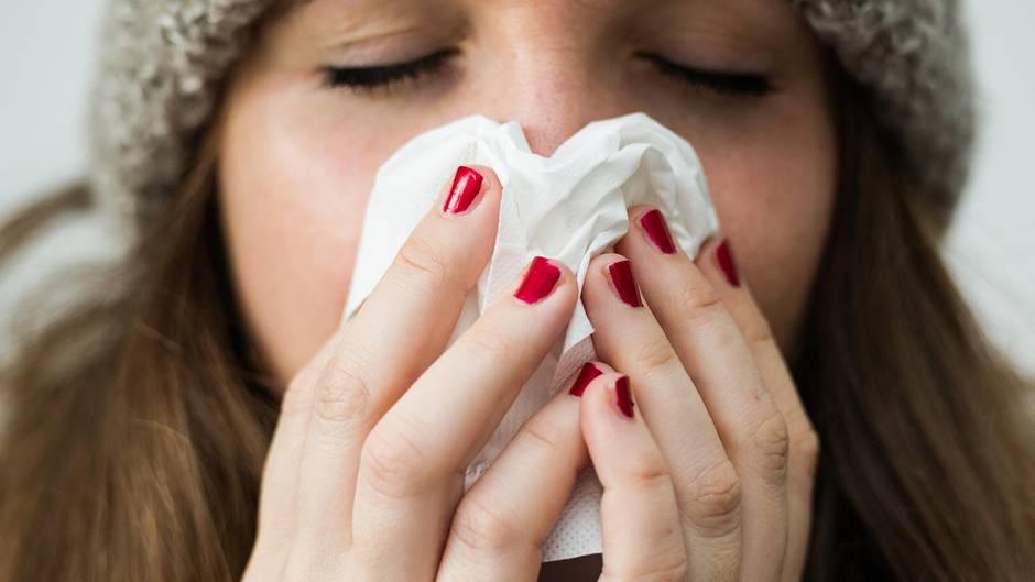 Grippe 2019: Eine Frau hält sich ein Taschentuch vor das Gesicht