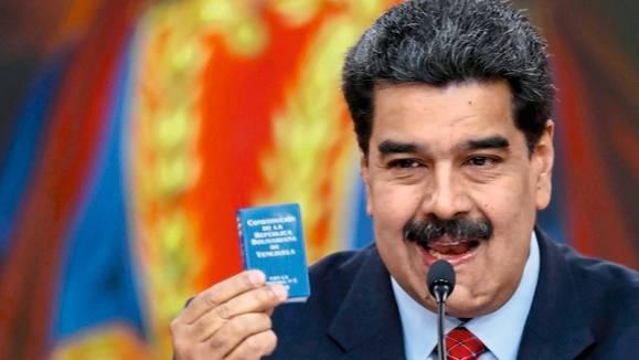 Der bisherige Machthaber Nicolás Maduro kontert in einer Rede mit der Verfassung als Büchlein und Bolívar in Öl
