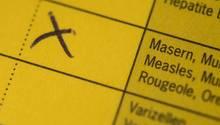 Ein Kreuz steht am auf einem Impfpass, in dem eine Kombiimpfung für Masern, Mumps und Röteln eingetragen ist