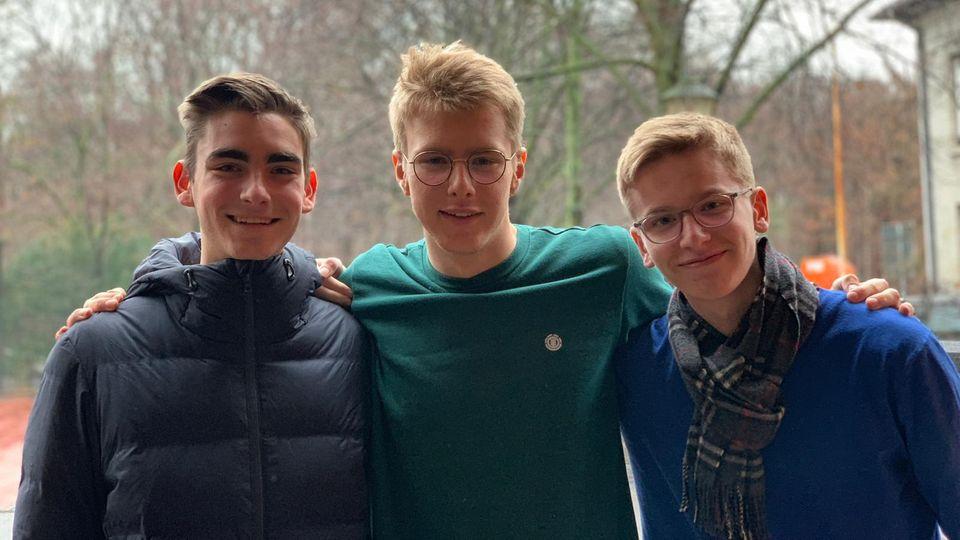 Die drei Erfinder stehen nebeneinander