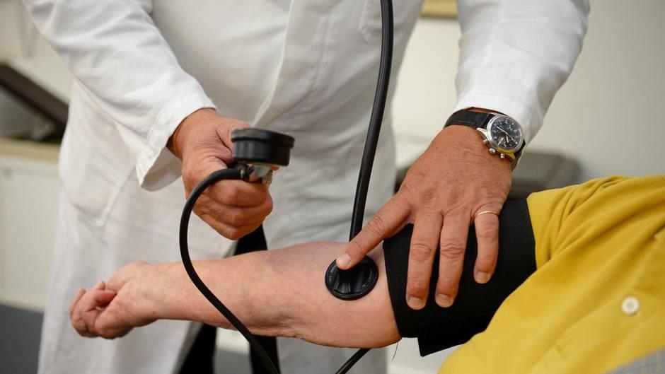 Ein Hausarzt misst in seiner Praxis einer Patientin den Blutdruck
