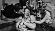 Nach einer Wassergeburt hält eine Mutter glücklich lachend ihr Baby im Arm, rund um das Wasserbecken freut sich die Familie