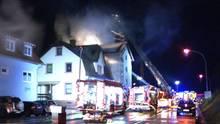 Feuerwehrleute löschen den Brand in einem Mehrfamilienhaus in Lambrecht in Rheinland-Pfalz