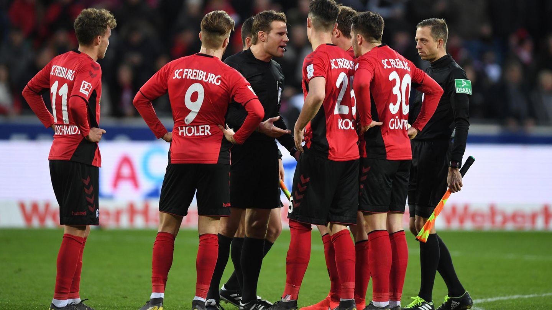 Schiedsrichter Felix Brych diskutiert mit Freiburger Spielern