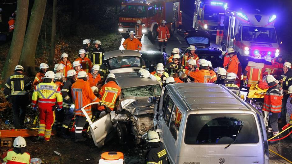 Einsatzkräfte der Feuerwehr stehen nach der Kollision eine Transporters und eines Pkw neben den Wracks