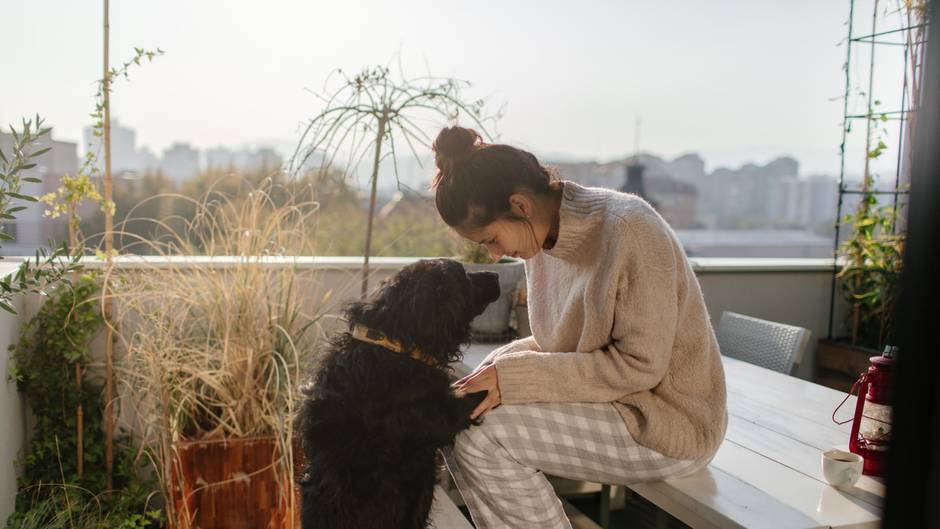 Frau mit Hund auf Balkon