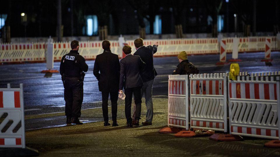 Im Dunkeln stehen drei junge Männer in Anzügen mit uniformierten Polizisten zwischen Baustellenabsperrungen. Einer zeigt etwas