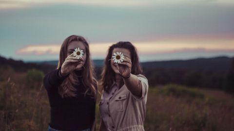 Zwei Freundinnen mit Blumen in der Hand
