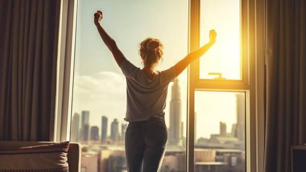 Vitamin D: Eine Frau steht vor einem Fenster und blickt in die Sonne