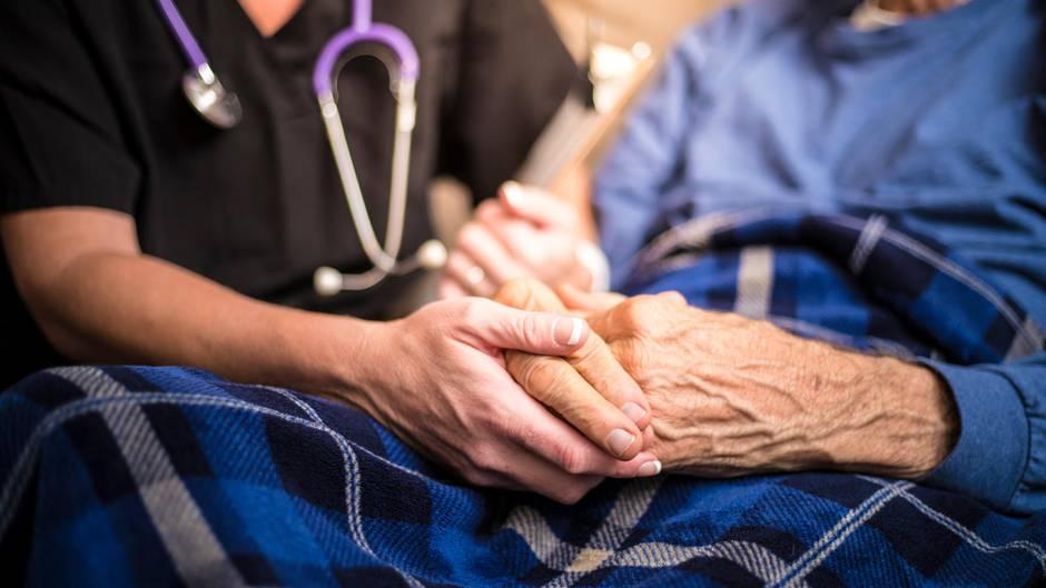 Eine Schwester hält die Hand einer älteren Dame