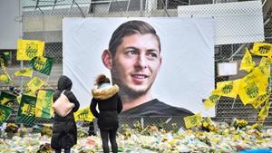 Blumen liegen vor einem Plakat, dass den argentinischen FußballstarEmiliano Sala zeigt
