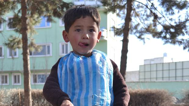 Murtasa Ahmadi 2018 in seinem Lionel-Messi-Trikot aus einer Plastiktüte