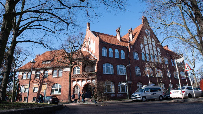 An einer Straßenecke steht ein Schulgebäude aus Backstein und mit einigen weißen Verzierungen