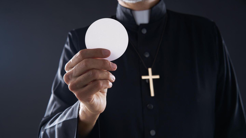Ein Pastor hält eine Hostie in der Hand