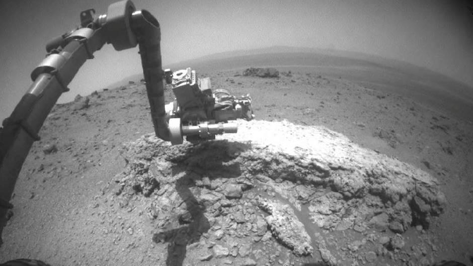 """Der Mars-Rover """"Opportunity""""greift mitseinemGelenkarm nach einem Stein, um diesenzu untersuchen. Der Roboter lieferte 2004die ersten Belege dafür, dass es früher Wasser auf dem Roten Planeten gegeben haben muss."""