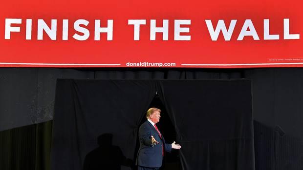 Donald Trump unter Finish the wall-Banner